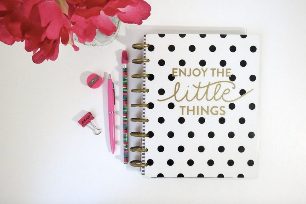 Black dotty notepad with pink pens next to it