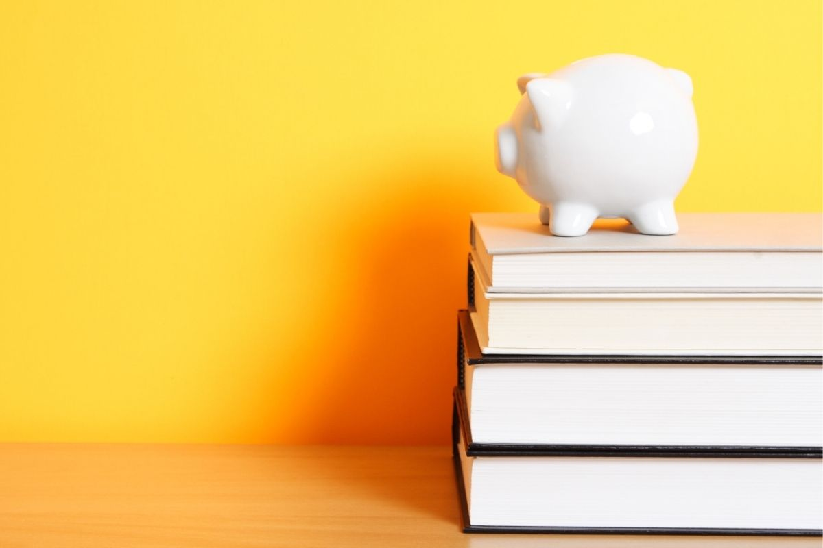 White piggy bank on books with a bright yellow background