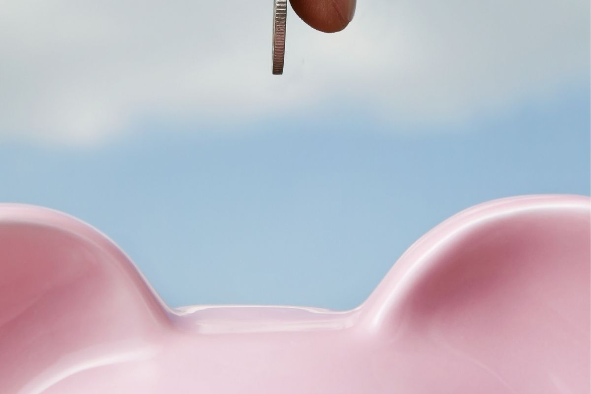 Blue background with someone putting a coin in a pink piggy bank
