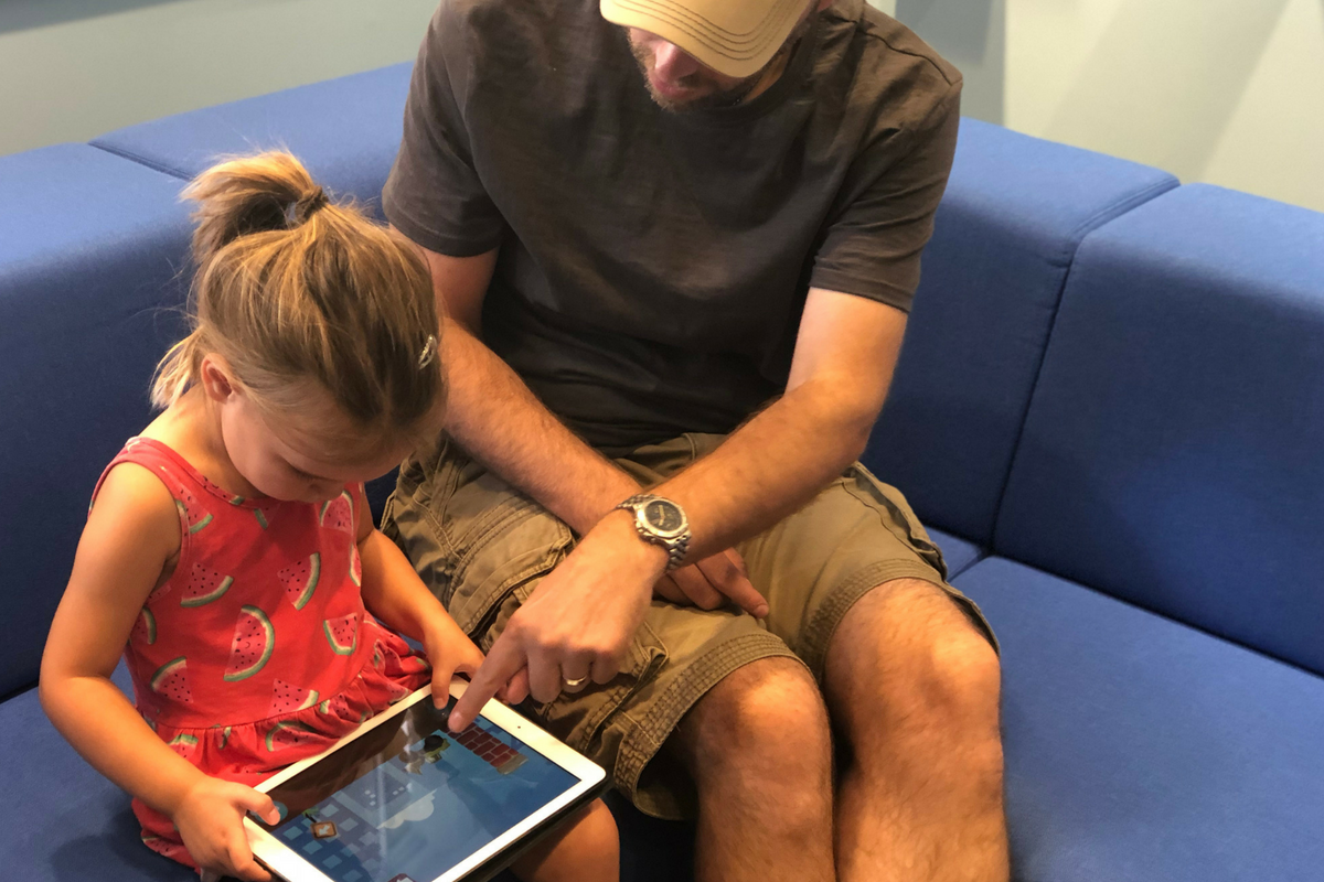 Child and father playing iPad