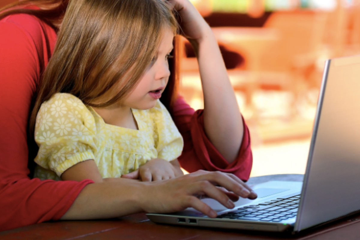 Child and mother sat at laptop