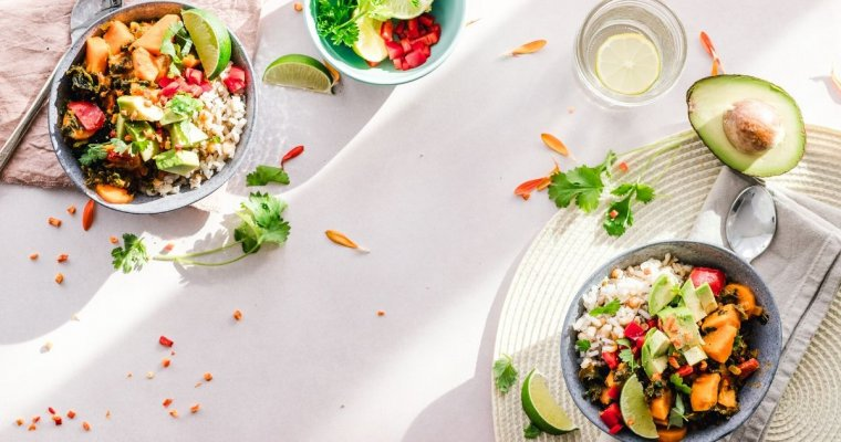 Three bowls of salad and rice on a white table cloth