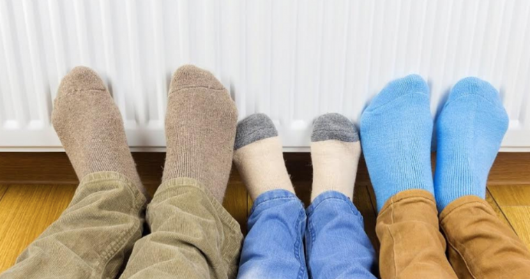 three sets of feet touching a radiator
