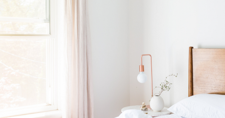 Pink curtains with a white wall and white gold lamps.