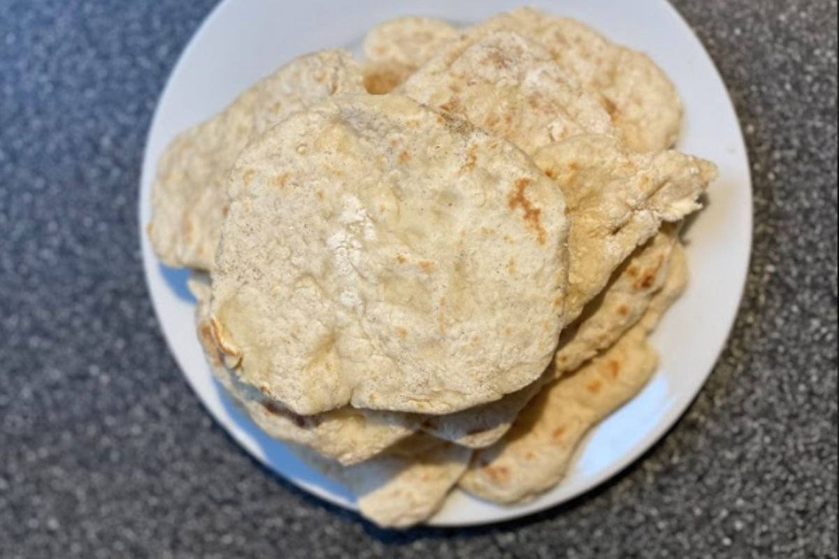Six naan breads on a white plate