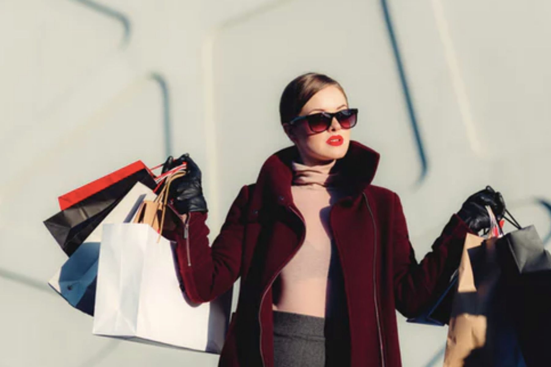 Woman in a red coat holding shopping bags