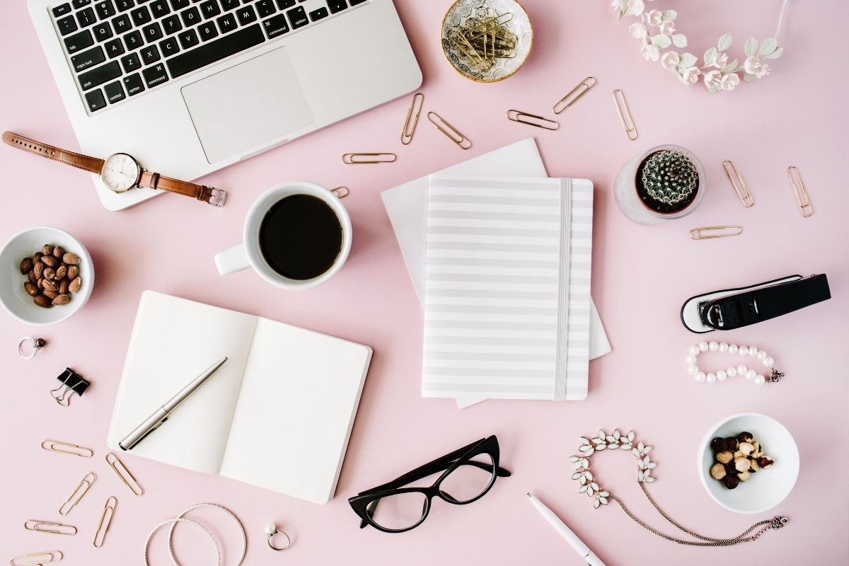 Pink background with laptop and office supplies