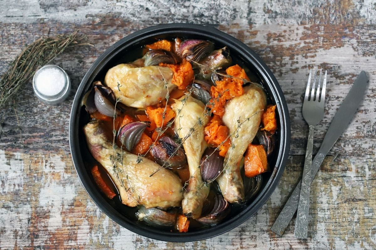 Chicken thighs in a slow cooker with carrots and red onions