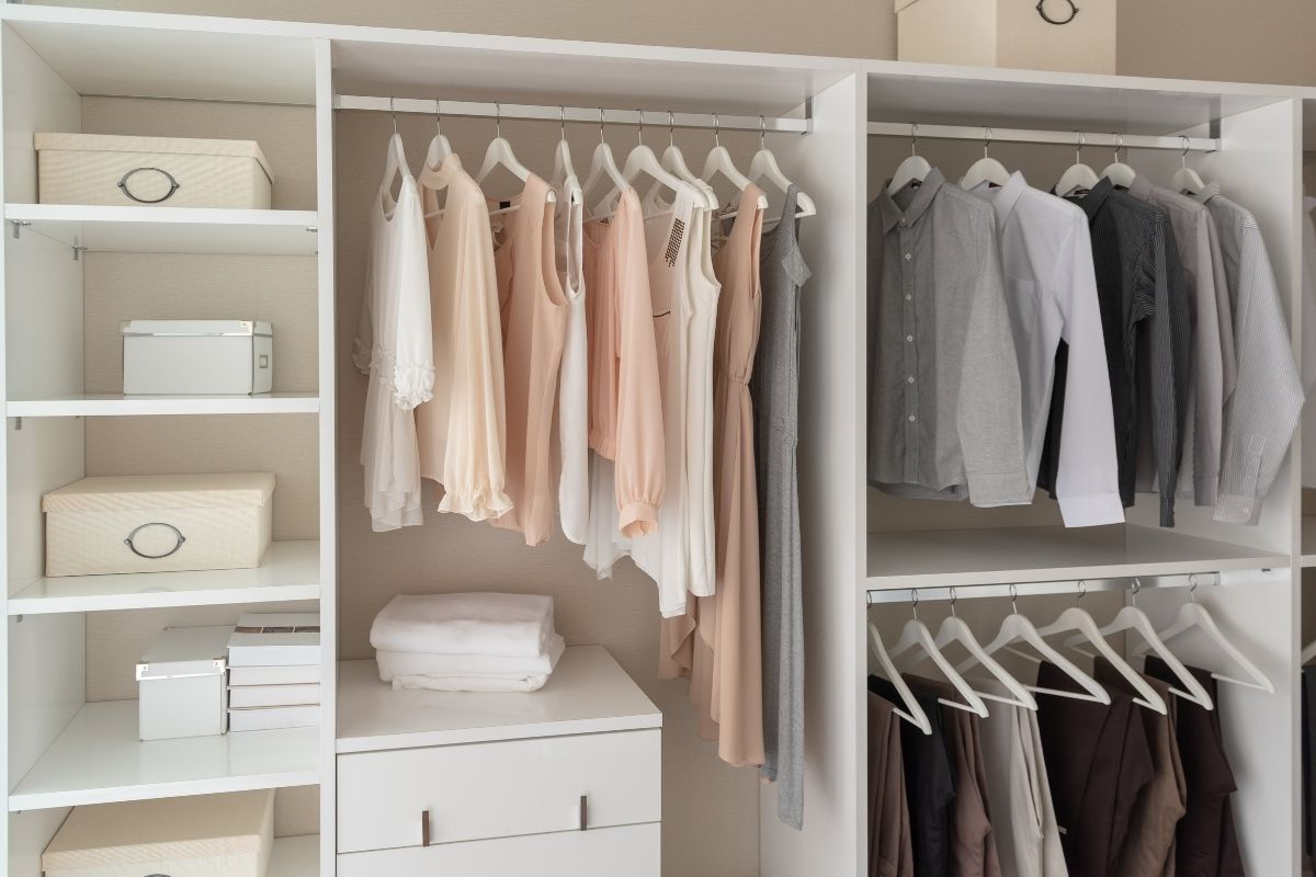White wardrobe with clothes hung up