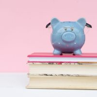 pink background with a blue pig on top of books