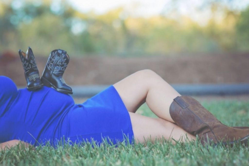 Woman laying in the grass with baby boots on her belly