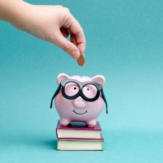 Blue background with piggy bank with glasses on